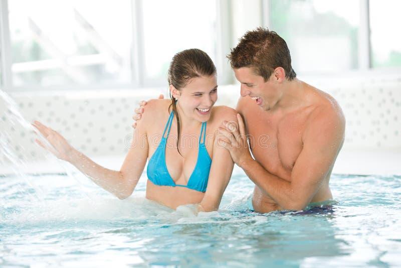 Os pares novos têm o divertimento sob o córrego da água na associação imagens de stock royalty free