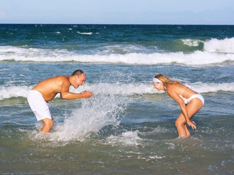 Os pares novos têm uma estadia do divertimento na praia foto de stock