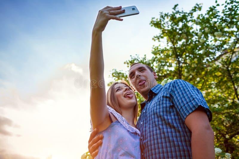 Os pares novos tremem e tomando o selfie no jardim da mola no por do sol Mulher e homem que mostram seus toungues Indivíduos que  fotografia de stock