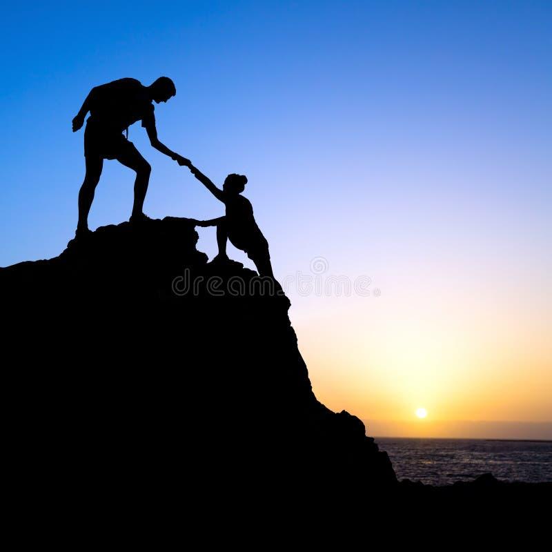 Os pares, o homem e a mulher ajudam a silhueta nas montanhas fotografia de stock