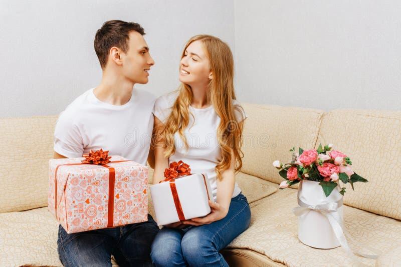Os pares, o homem e a mulher novos dão-se presentes ao sentar-se em casa no sofá, conceito do dia de Valentim imagem de stock