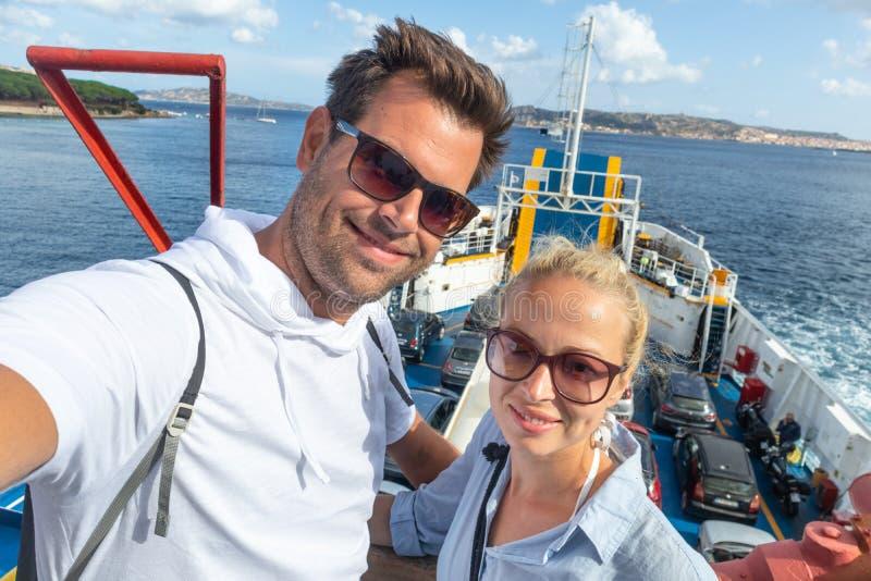 Os pares ocasionais que tomam a foto do autorretrato do selfie no ferryboat tropeçam a seu destino da ilha das férias de verão imagens de stock royalty free