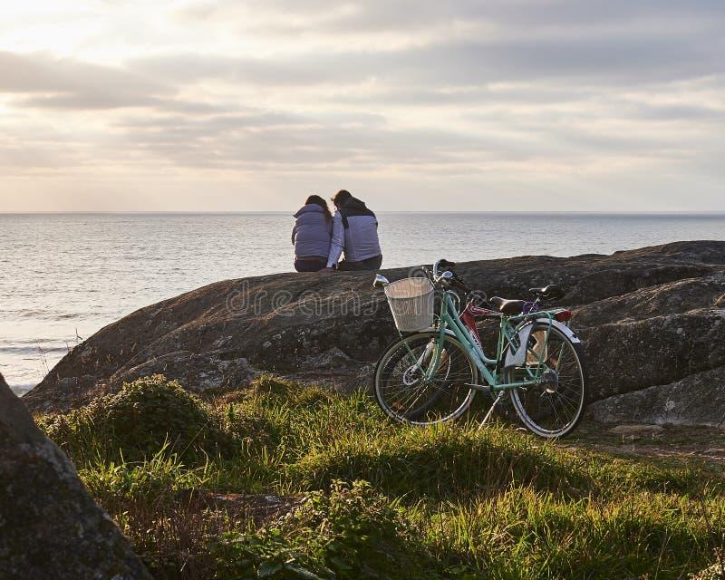 Os pares olham o por do sol após o passeio da bicicleta imagem de stock royalty free