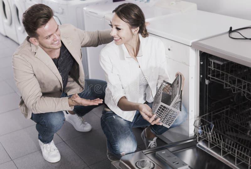 Os pares que olham máquinas de lavar louça em dispositivos domésticos compram imagens de stock royalty free