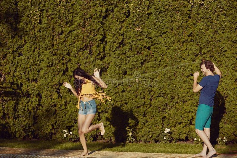 Os pares que têm o divertimento derramam-se com mangueira de jardim imagens de stock