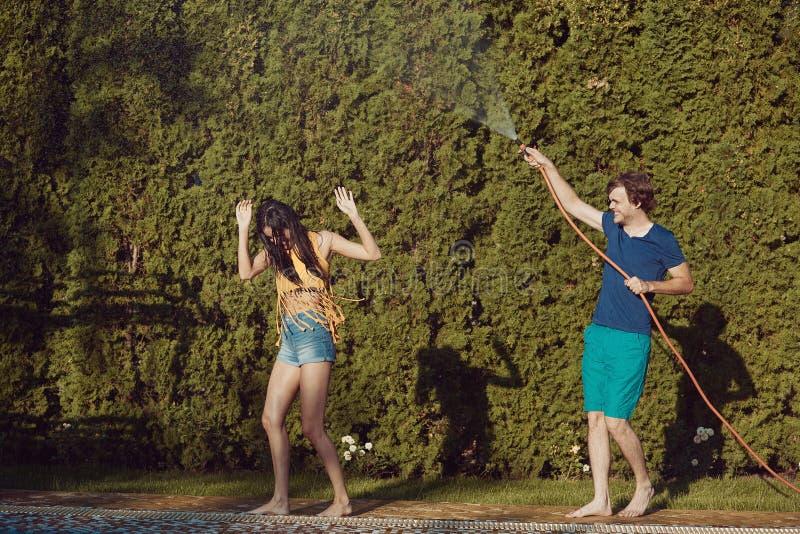 Os pares que têm o divertimento derramam-se com mangueira de jardim imagens de stock royalty free