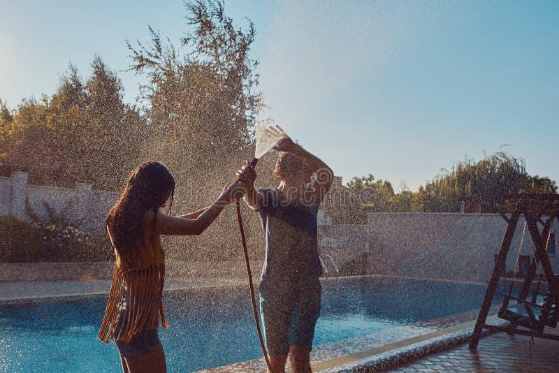 Os pares que têm o divertimento derramam-se com mangueira de jardim foto de stock royalty free