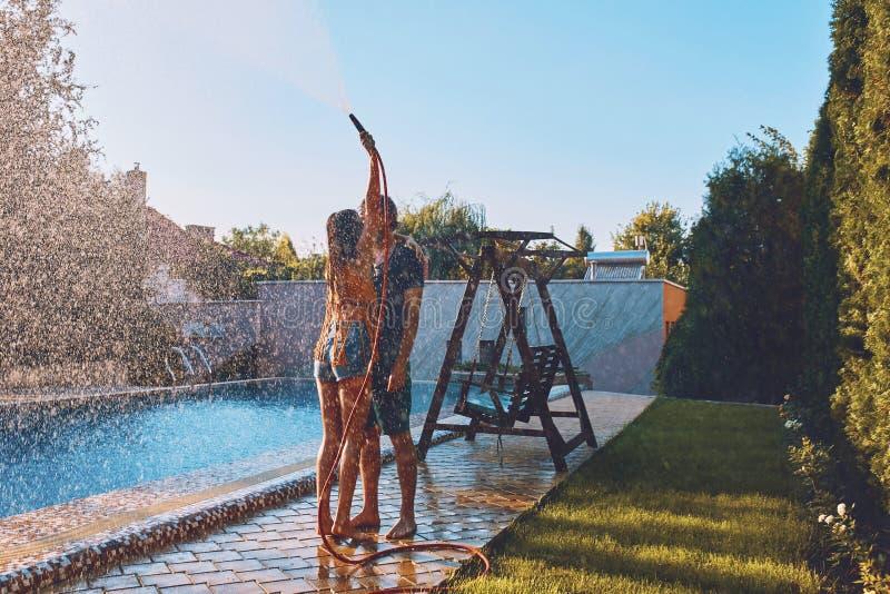 Os pares que têm o divertimento derramam-se com mangueira de jardim fotos de stock