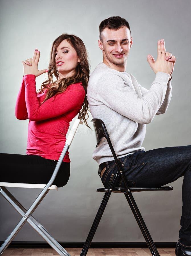 Os pares que têm o divertimento fingem as mãos que os dedos são armas fotografia de stock royalty free