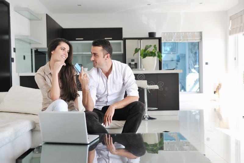 Os pares relaxam e trabalham no computador portátil em casa imagem de stock
