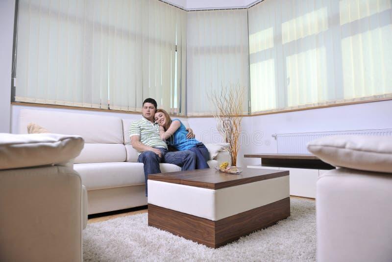 Os pares relaxam em casa no sofá na sala de visitas fotos de stock