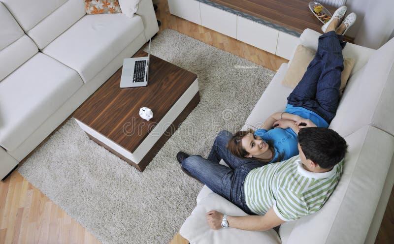 Os pares relaxam em casa no sofá na sala de visitas fotografia de stock