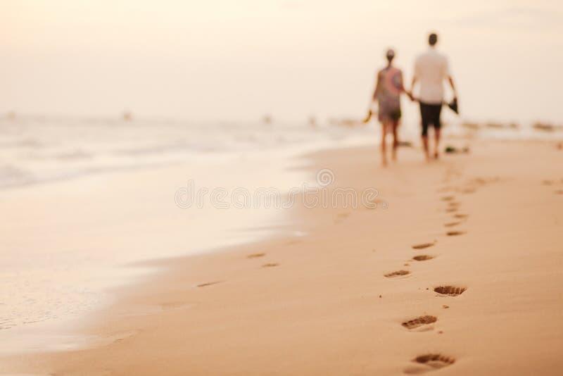 Os pares relaxam na praia junto fotos de stock