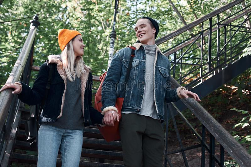 Os pares românticos felizes de turistas são de descida e guardando as mãos em etapas fotografia de stock royalty free