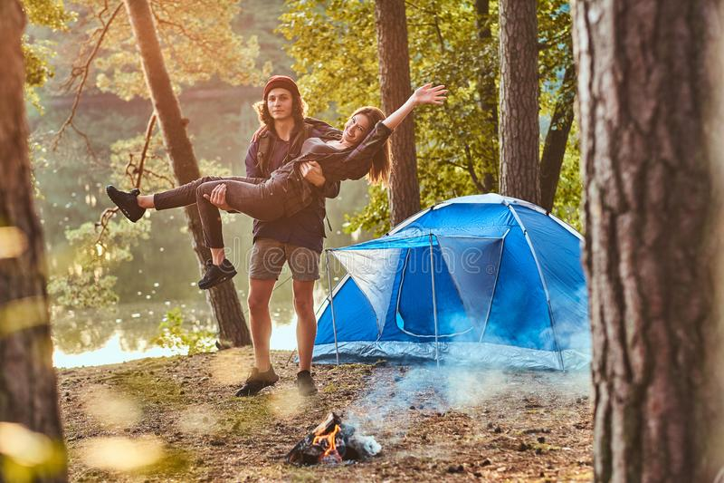 Os pares românticos novos têm o divertimento na floresta do verão perto de sua barraca imagens de stock royalty free