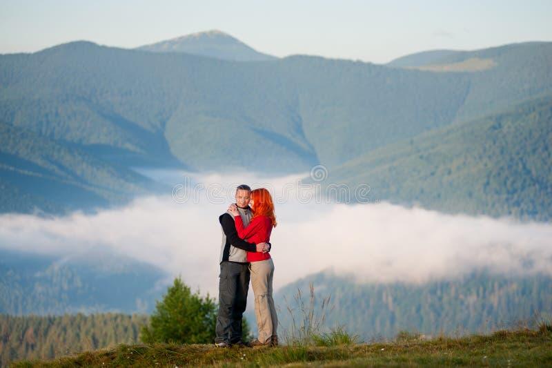 Os pares românticos que apreciam uma manhã haze sobre as montanhas fotografia de stock royalty free