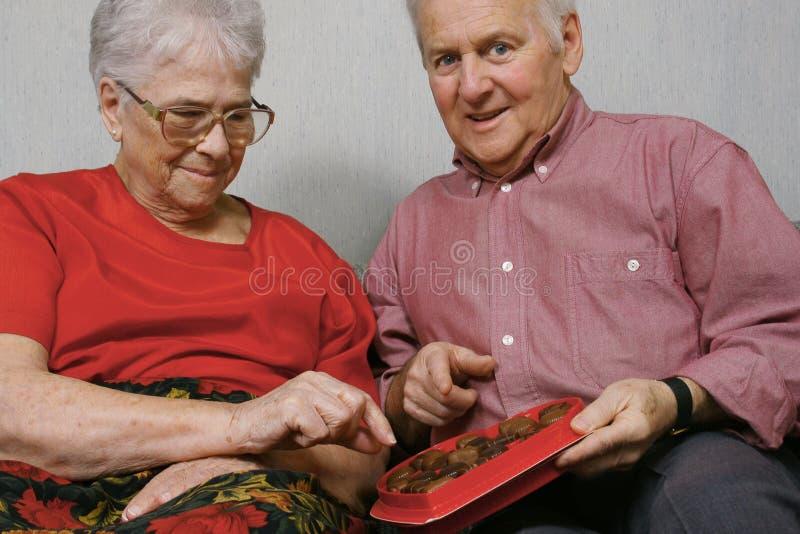 Os pares sênior comem o chocolate foto de stock royalty free