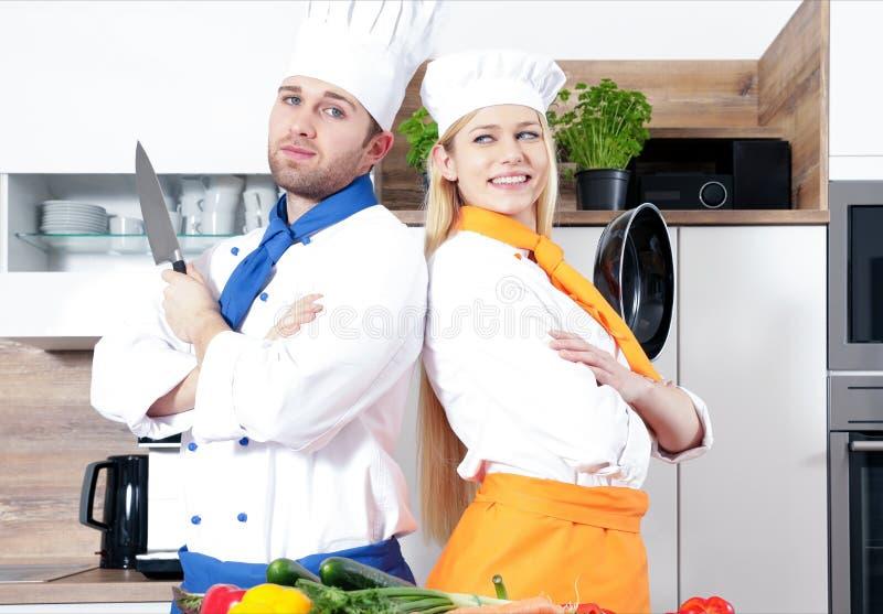 Os pares 'sexy' bonitos do homem da mulher como um cozinheiro estão cozinhando em uma cozinha imagens de stock royalty free