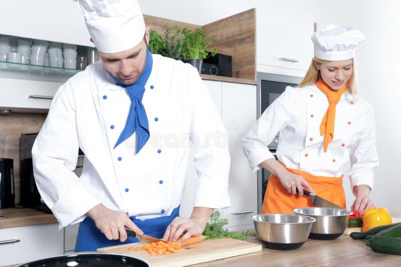 Os pares 'sexy' bonitos do homem da mulher como um cozinheiro estão cozinhando em uma cozinha imagens de stock