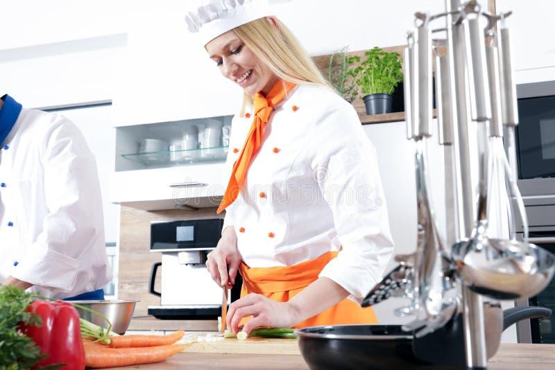 Os pares 'sexy' bonitos do homem da mulher como um cozinheiro estão cozinhando em uma cozinha fotografia de stock royalty free