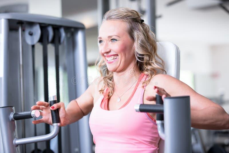 Os pares 'sexy' bonitos do homem da mulher estão fazendo um exercício no gym dos fitnes - imprensa da caixa, banco imagens de stock