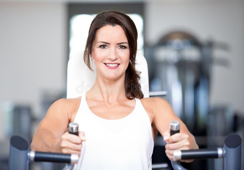 Os pares 'sexy' bonitos do homem da mulher estão fazendo um exercício no gym dos fitnes - imprensa da caixa, banco foto de stock royalty free