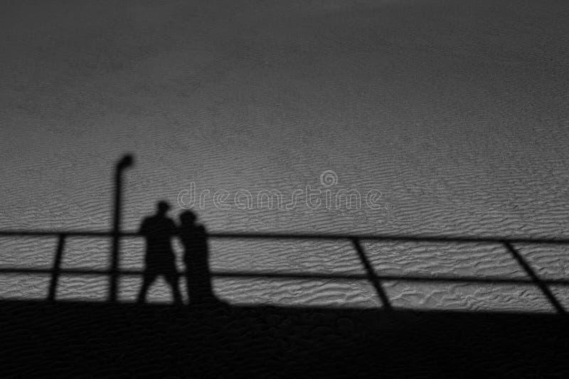 Os pares sombreiam na areia fotografia de stock