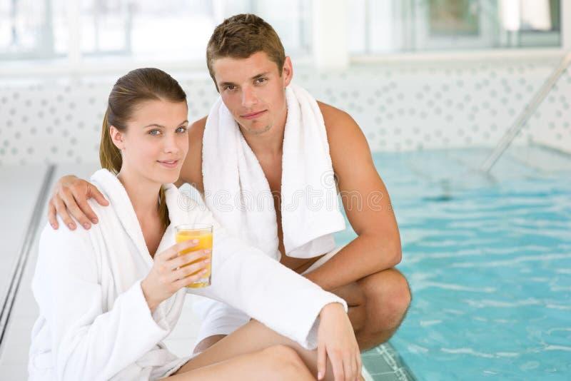 Os pares sportive novos relaxam na piscina fotos de stock royalty free