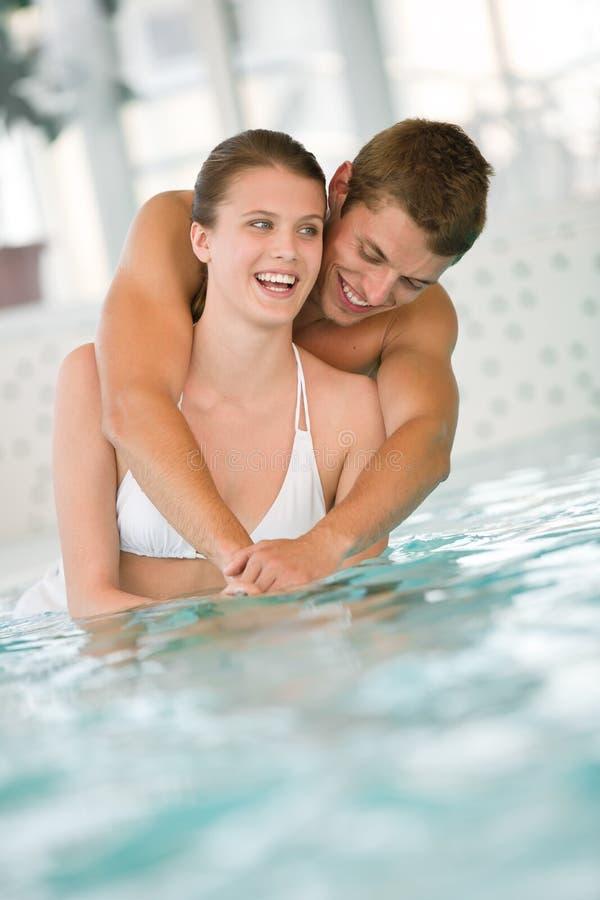 Os pares sportive novos têm o divertimento na piscina fotos de stock