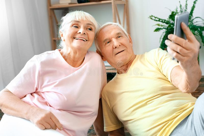 Os pares superiores exercitam junto em casa as fotos do selfie dos cuidados médicos felizes foto de stock