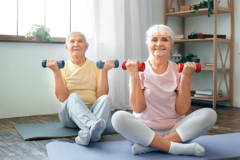 Os pares superiores exercitam junto em casa cuidados médicos levantam acima pesos foto de stock