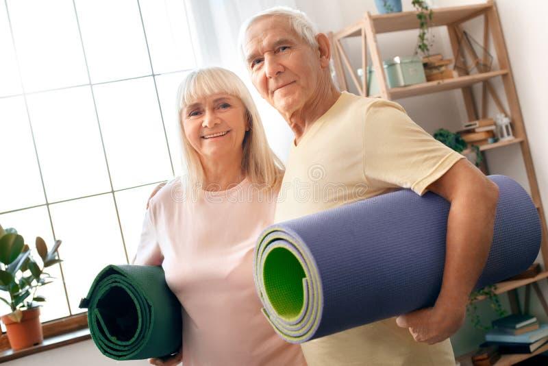 Os pares superiores exercitam junto em casa os cuidados médicos que guardam as esteiras da ioga que olham a câmera foto de stock