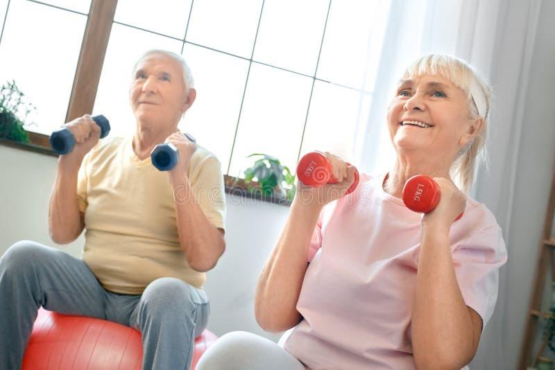 Os pares superiores exercitam junto em casa fazendo a ginástica aeróbica que guarda dubbells fotografia de stock