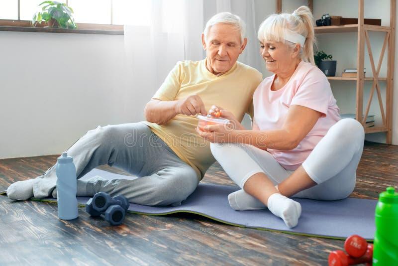 Os pares superiores exercitam junto em casa a nutrição saudável dos cuidados médicos foto de stock royalty free