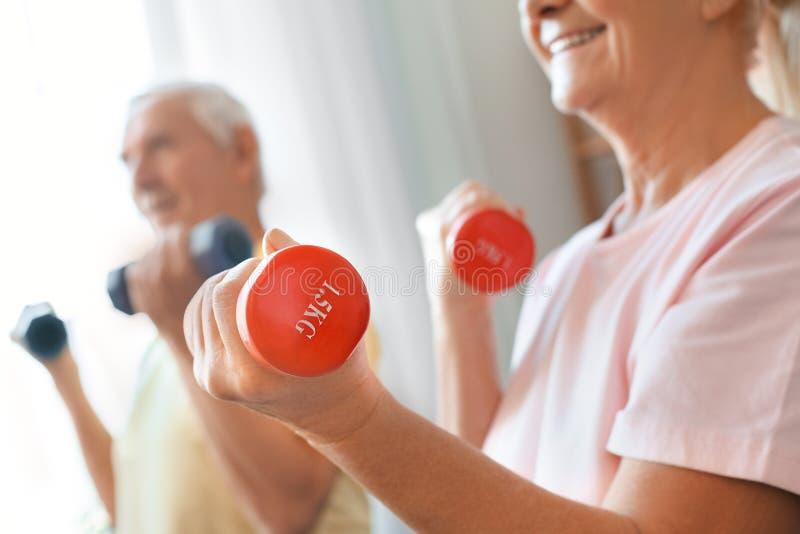 Os pares superiores exercitam junto em casa o close-up dos pesos dos cuidados médicos imagem de stock