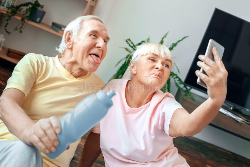 Os pares superiores exercitam junto em casa o grimase das fotos do selfie dos cuidados médicos fotos de stock royalty free