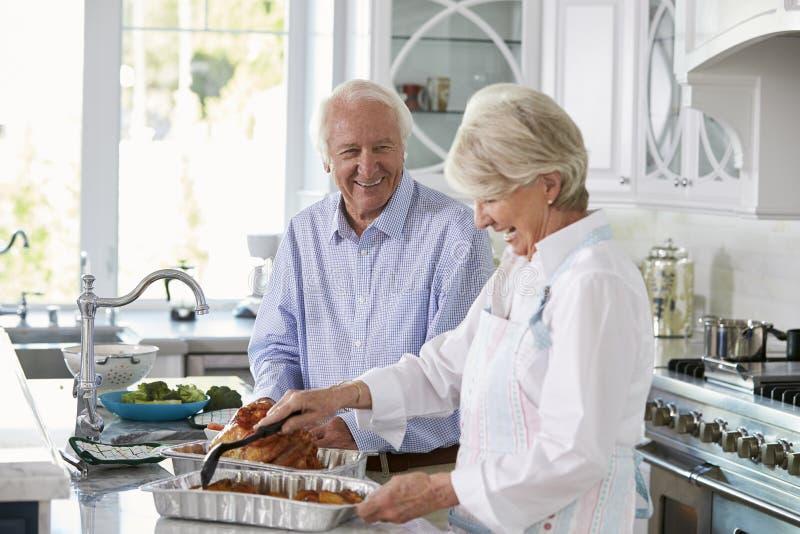 Os pares superiores fazem a refeição de Turquia do assado na cozinha junto fotos de stock