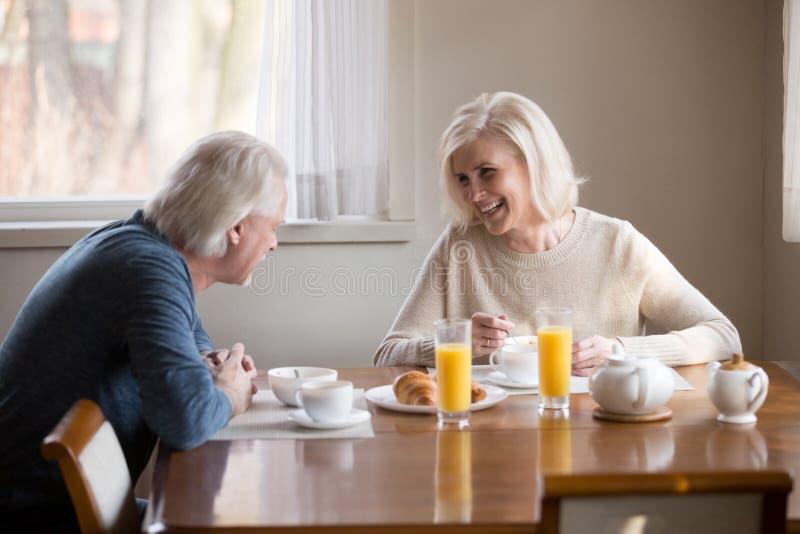 Os pares superiores loving de sorriso que têm a manhã saudável tomam o café da manhã em foto de stock