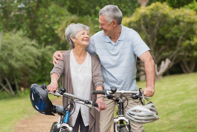 Os pares superiores no ciclo montam no parque fotos de stock royalty free