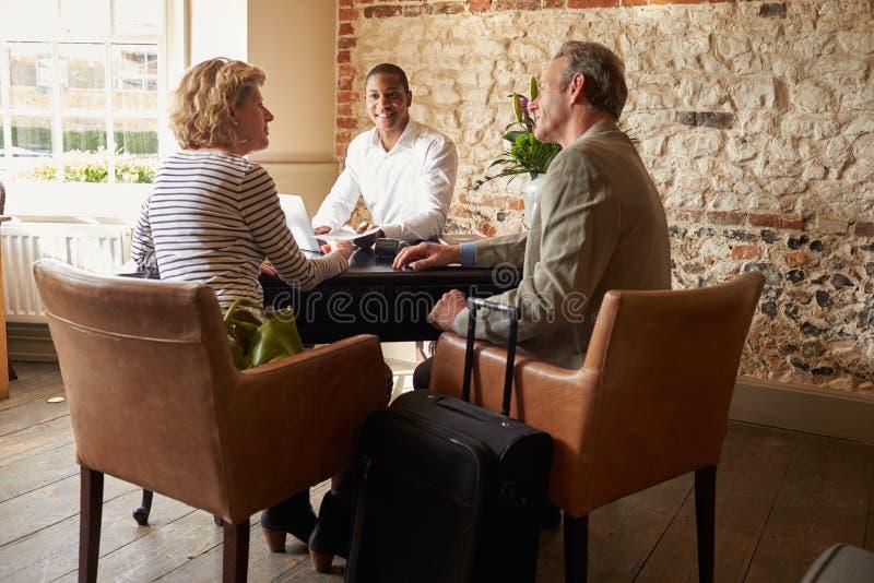 Os pares superiores no hotel verificam dentro a mesa, comprimento completo foto de stock