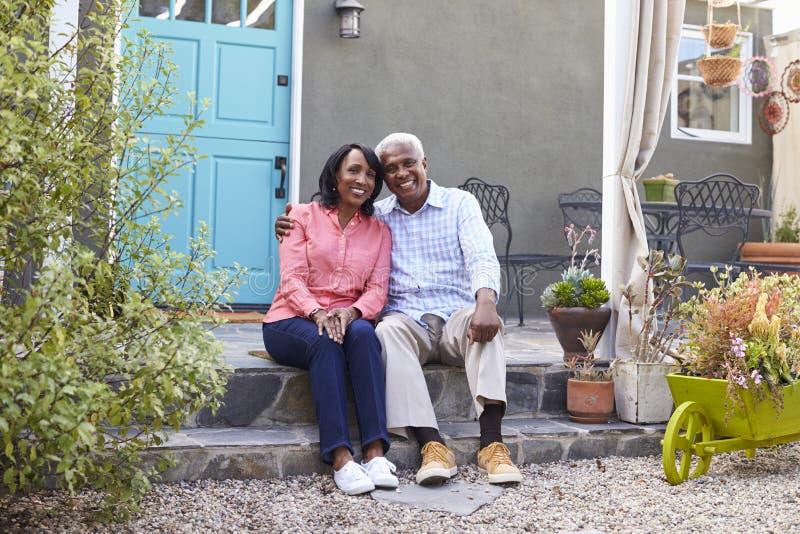 Os pares superiores sentam-se em etapas fora de sua casa, comprimento completo fotografia de stock royalty free