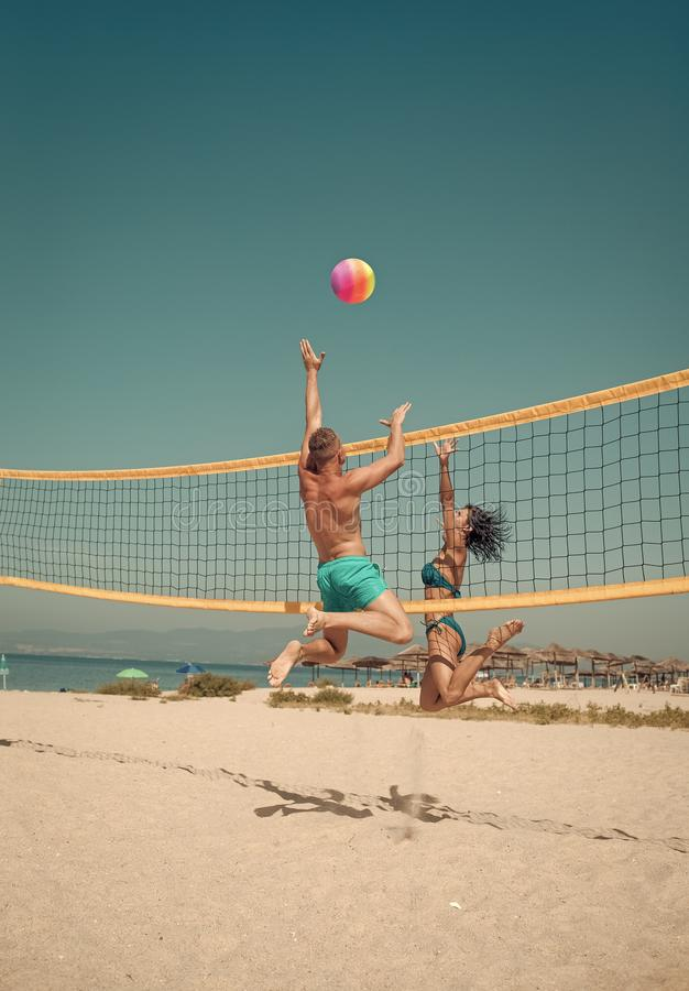 Os pares têm o divertimento que joga o voleibol Os pares ativos desportivos novos bateram fora da bola da salva, jogo do jogo no  fotos de stock royalty free