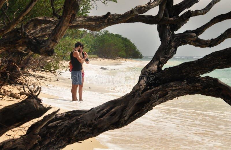 Os pares tomam imagens em uma praia foto de stock