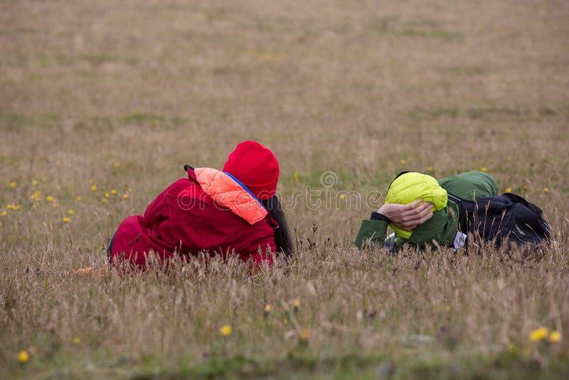 Os pares, um homem e uma mulher, encontrando-se ao redor na grama amarela fotografia de stock royalty free