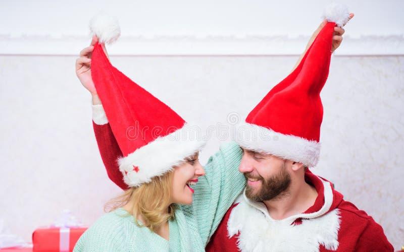 Os pares vestem chapéus como o fundo da árvore de Natal de Papai Noel É fácil espalhar ao redor a felicidade A família feliz come foto de stock royalty free