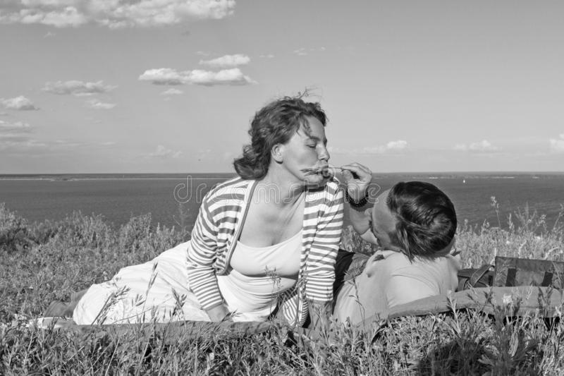 Os pares vestiram o encontro ocasional junto no gramado na grama do verão no banco de rio sob o céu azul e as nuvens fotografia de stock royalty free