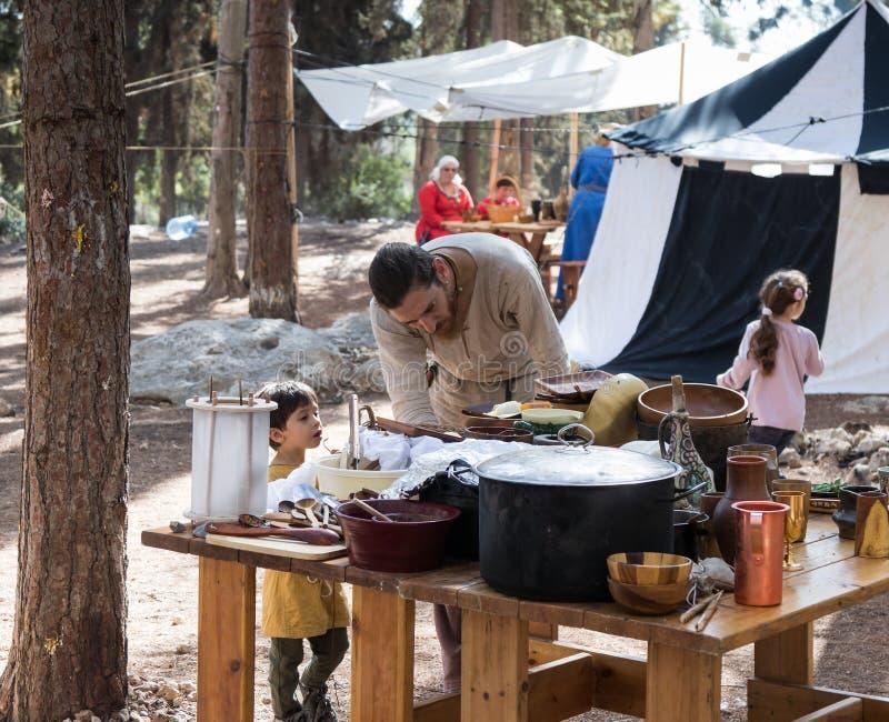Os participantes da reconstrução do ` de Viking Village do ` que prepara o alimento no acampamento na floresta perto de Ben Sheme fotografia de stock royalty free