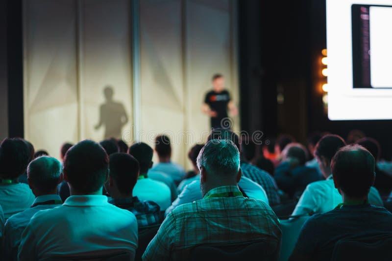 Os participantes de confer?ncia, eventos, apresenta??es, escutam o orador que senta-se nas cadeiras imagens de stock
