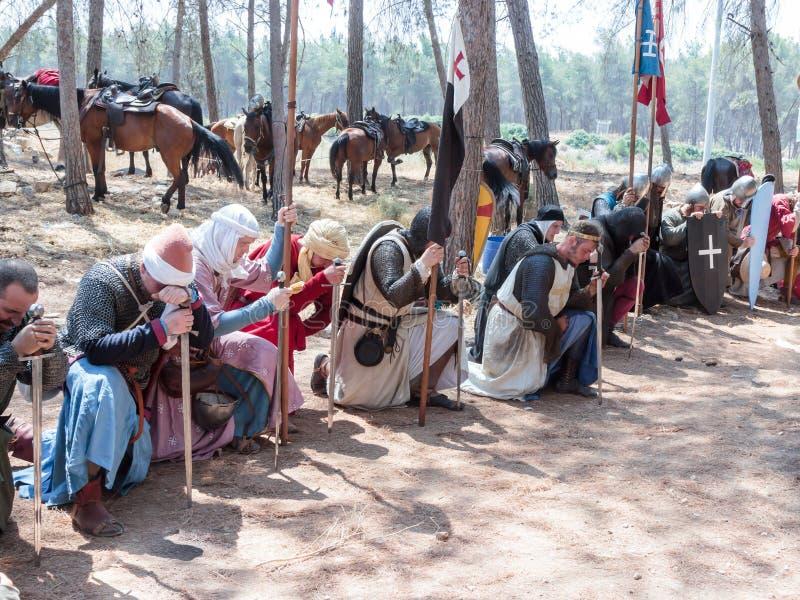 Os participantes na reconstrução dos chifres da batalha de Hattin em 1187 no papel dos cruzados rezam no acampamento antes do aca imagens de stock royalty free