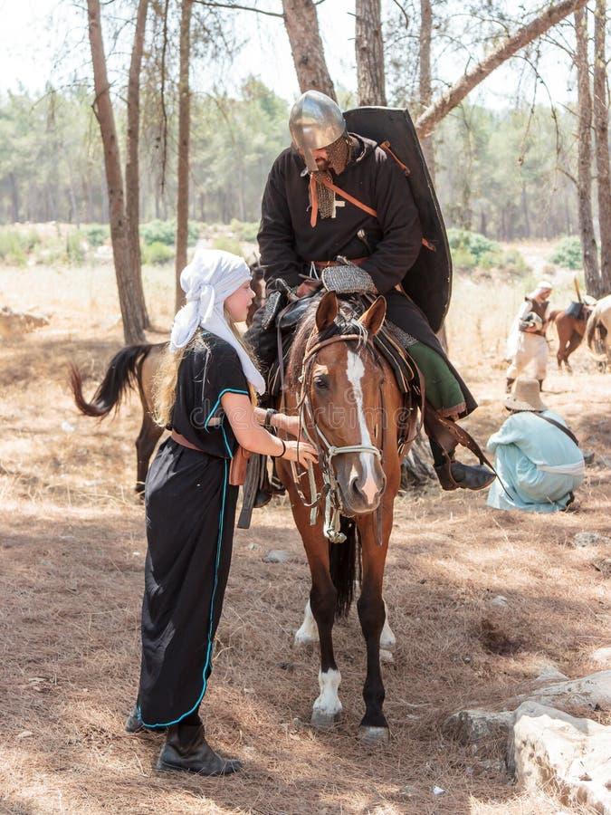 Os participantes na reconstrução dos chifres da batalha em 1187 uma de Hattin sentam-se em um cavalo da batalha, e segundo guarda fotografia de stock